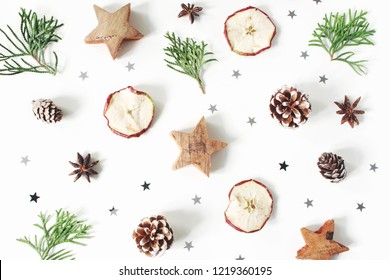 Christmas festive styled composition. Decorative pattern. Pine cones, dried apple fruit, cypress branches, anise, confetti and wooden stars isolated on white wooden background. Flat lay, top view