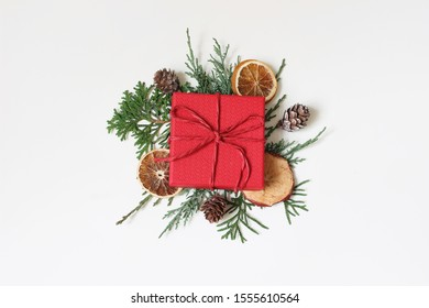 Christmas festive styled stock image composition. Red wrapped gift box, cypres branches, dry apple, orange fruit and pine cones isolated on white table background. Winter holiday. Flat lay, top view.