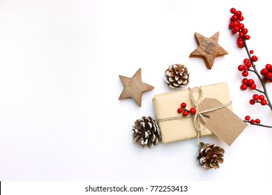 Christmas festive styled stock image. Floral frame composition with gift box, craft paper tag, pine cones, eucalyptus branches, wooden stars and holly berries on white wooden background. Flat lay, top
