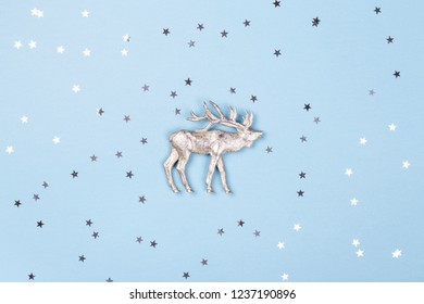 Christmas figurine of reindeer and silver confetti on blue background. Minimal New Year card, top view.