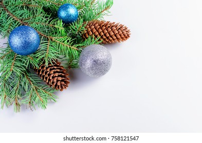 Christmas fir branches, blue and silver balls, cones, Blue and white color Christmas decorations on the white  background  copy space