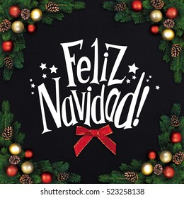 Christmas fir branches with decorations on a black background and greetings text Feliz Navidad!