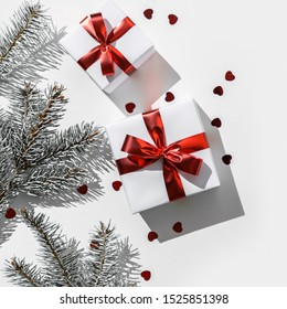Christmas fir branches with gift boxes with red ribbon on white paper background with bokeh, light. Xmas and New Year greeting card, winter holiday. Flat lay, top view, harsh shadow