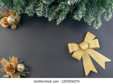 Christmas fir tree branch with cone pine and bowknot on a dark background. Top view with copy space for text.