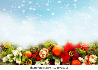Christmas fir tree branch covered by snow and bauble decor on stone background. Xmas backdrop for your greeting card with space for text.