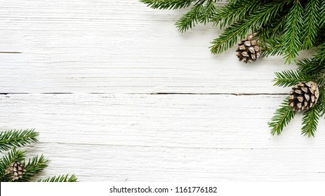 Christmas Fir tree branches and pine cones on white wooden rustic background.