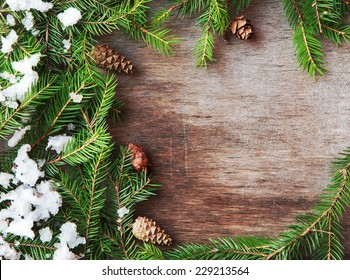 Christmas fir tree with cones and snow on a wooden background, selective focus and place for text. Toned