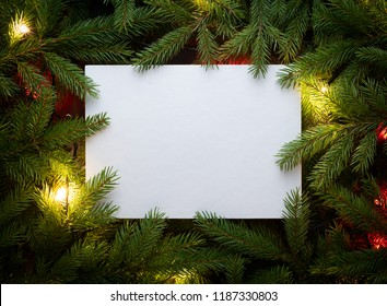 Christmas fir tree with garland. Flat lay, top view, copy space. Decorative frame of fir branches and paper card note