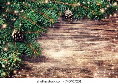 Christmas fir tree on a wooden background and bokeh light