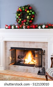 Christmas fireplace with colorful decorations and and a traditional Xmas wreath above a blazing fire in the hearth for a warm cozy seasonal celebration