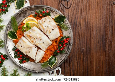 Christmas fish. Roasted cod pieces, served in vegetable sauce. Xmas styling. Top view.