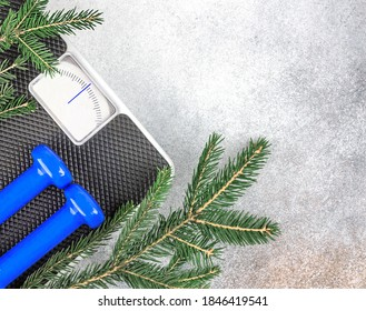 Christmas fitness background. Blue dumbbells, scales with empty display and a spruce branch. The concept of sports lifestyle, weight loss. Copy space. Top view.
