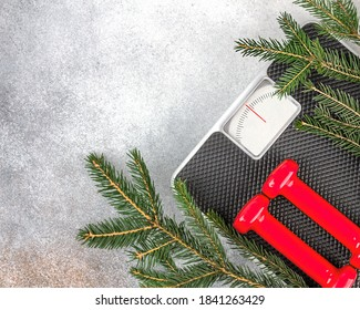 Christmas fitness background. Red dumbbells, scales with empty display and a spruce branch on a gray background. The concept of sports lifestyle, weight loss. Copy space. Top view.