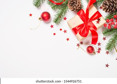 Christmas flat lay background with fir tree branch, pine cones, present box and red decorations on white.