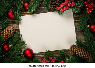 Christmas flat lay background with fir tree branch, present box and red decorations. Free space for design.