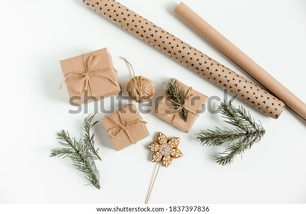 Christmas flat lay with fir pine branches,gift boxes,brown twine,gingerbread,and wrapping paper on the white background. Christmas preparation, gift wrapping concept