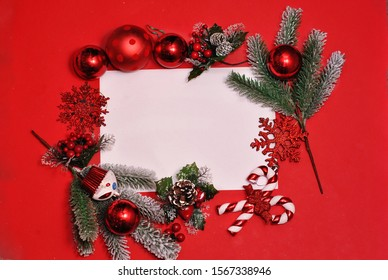 Christmas flat lay frame made from decorations silver and white color on the red background. Toys decoration fir, spruce, fir-tree, balls, snowflake, lollipop with white copy space for text. Winter