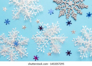 Christmas flat lay of multicolored snowflakes against blue background. Winter concept. New Year's holiday pattern