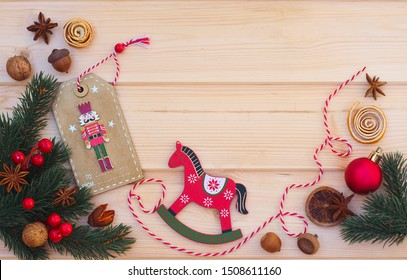 Christmas flat lay on a wooden background. Wooden Christmas toys and Christmas decor. Nutcracker and wooden horse