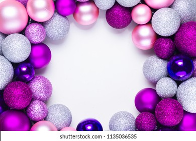 Christmas flat lay round frame with silver, pink abd violet glass balls and gift box, copy space on white desk