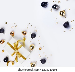 Christmas flat lay scene with golden, gray and black glass balls and gift box with copy space on white background