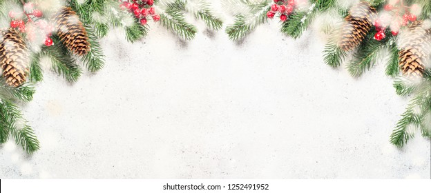Christmas flatlay background with fir tree brunch and red decorations on white stone background. Long banner format with empty space for your design.
