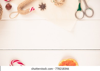 Christmas flatlay with candy canes, hazelnuts, anise and scissors. Space for text. White background.