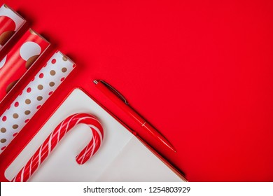 Christmas flatlay with clean note pad, red pen, wrapping paper and candy canes on the bright red background.
