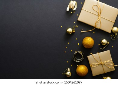 Christmas Flatlay composition. Black Xmas background with golden decorations, gifts box, balls, confetti. Christmas poster, greeting card template, web banner mockup. Flat lay, top view, copy space