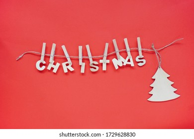 Christmas flatley, the wooden word Christmas and a Christmas tree hanging on a string on a bright red background. natural decoration for the holidays.
