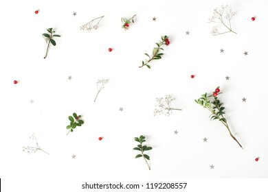Christmas floral pattern. Winter composition of red cranberry branches, baby's breath flowers and silver confetti stars on white table. Festive background. Flat lay, top view.