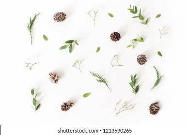Christmas floral pattern. Winter composition of eucalyptus leaves and branches, larch cones and baby's breath flowers on white table background. Flat lay, top view.