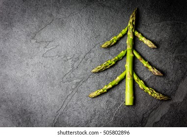 Christmas Food background. Christmas tree made from fresh asparagus on black stone slate background. Healthy holiday food, vegan, vegetarian and diet concept