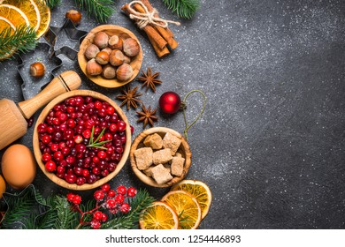 Christmas food baking background. Cranberry, orange, sugar, spices on black stone background. Top view copy space.