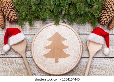 Christmas food concept - with xmas tree drawing in flour on round wooden plate andsanta hat spoons