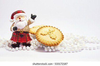 Christmas food and decoration with Santa and mince pies on white background for festival of christmas and new year. Holidays season.