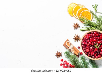 Christmas food drink background. Ingredients for cooking - cranberry, rosemary, orange and  anise on white background. Top view copy space.