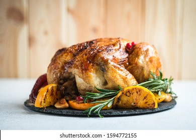 Christmas food. Fried chicken with orange, cranberries, garlic and rosemary on a light background. Festive table with Christmas decorations.