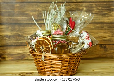 Christmas food gift baskets. Edible Christmas gift made of cookies, honey, homemade handmade sweets, dried oranges, lollipops on a wooden table.Concept handmade christmas gifts, Handmade food presents - Shutterstock ID 1839289063