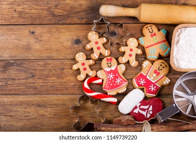 Christmas food. Homemade gingerbread cookies with ingredients for christmas baking and kitchen utensils on wooden table, top view
