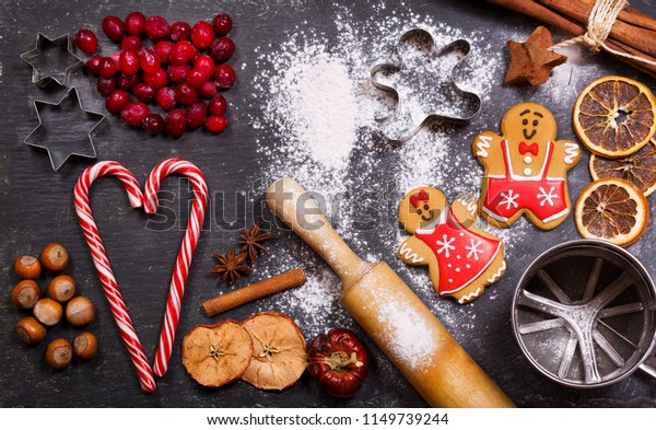 Christmas food. Homemade gingerbread cookies with ingredients for christmas baking and kitchen utensils on dark table, top view