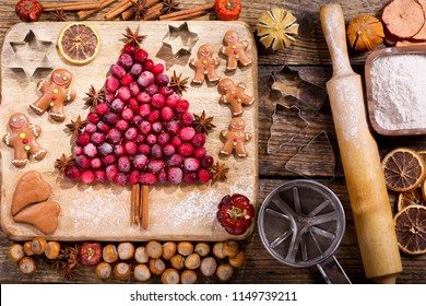 Christmas food. Ingredients for cooking Christmas baking: fir tree made from frozen cranberries, gingerbread cookies, kitchen utensils and dried fruits on a wooden table, top view