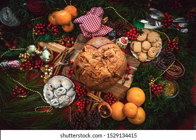Christmas Food. Christmas ingredients table with a Panettone in the center on a wooden board, accompanied by orange, cookies, cinnamon, pine. Festive pine decoration on red rustic background, top view