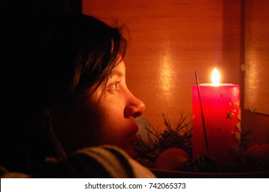 Christmas fortune telling. A girl looks at her reflection in a mirror by candlelight. Soft selective focus, candle lighting.