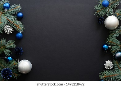 Christmas frame border with blue and sliver modern decorations, baubles, fir tree branches on dark black background. Elegant Christmas banner mockup, greeting card template
