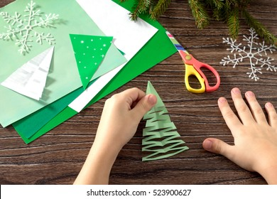Christmas frame. The child makes paper fir tree. Scissors, paper on a wooden table. Made with his own hands. Children's art project, a craft for children. Craft for kids.