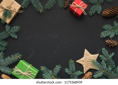 Christmas frame of colourful gift boxes, fir branches and cones on black background
