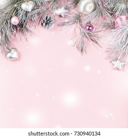Christmas frame with fir branches, conifer cones, silver ornaments on pastel background with snow falling