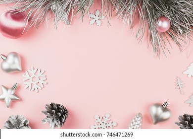 Christmas frame with fir branches, conifer cones, christmas balls and silver ornaments on pastel pink background, copy space