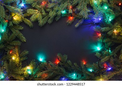 Christmas frame with fir branches and Christmas lights on black background. Copy space for text